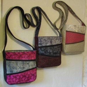 Tre unika väskor i rosa, svart och grått.